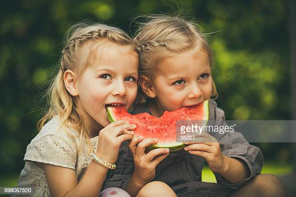 little twin girls eating melon
