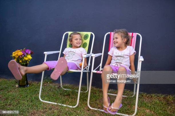 little twin girls sitting on garden chairs - cadeira dobrável - fotografias e filmes do acervo