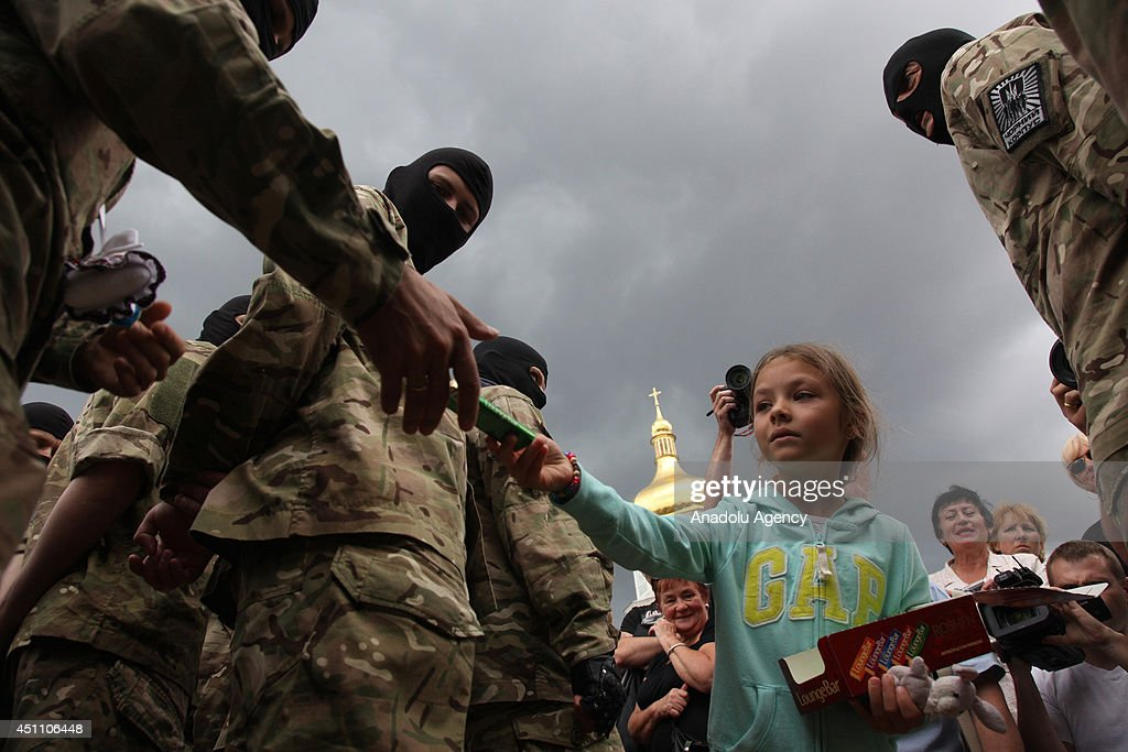 A little Ukrainian girl gives a present to a new soldier of Ukrainian army battalion 'Azov' during an oath of allegiance ceremony near the monument to Bogdan Khmelnitsky in the center of Kiev, Ukraine on June 23, 2014.