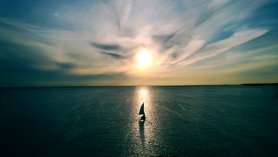 Little white boat floating on the water towards the horizon in the rays of the setting sun. Beautiful clouds with yellow highlights. Aerial view 869984486