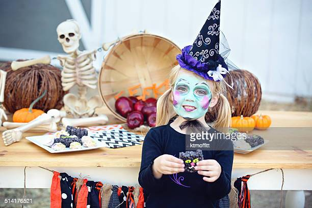 little witch holding cookie in front of halloween table - cat skeleton stock photos and pictures