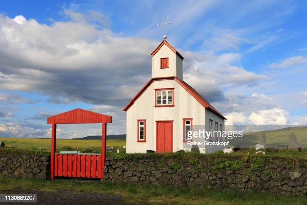 Little wooden church with red roof and red door