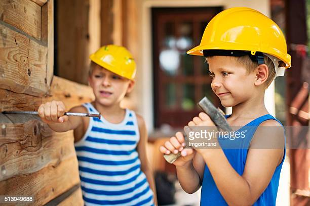 Little workers hammering a big nail together.