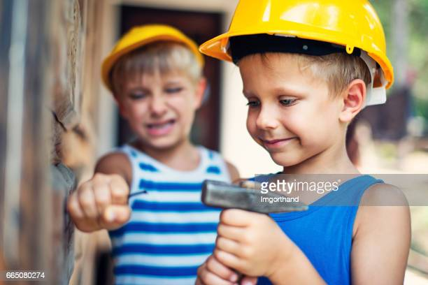 Little workers hammering nail together