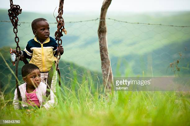 Little Xhosa girl and boy sitting in swing