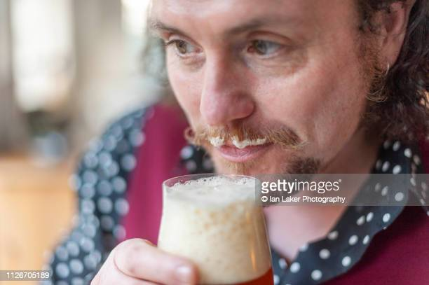 littlebourne, canterbury, england. 20 january 2019. bearded male with froth on moustache holding a glass of craft beer in an interior domestic setting - help:ipa stock pictures, royalty-free photos & images
