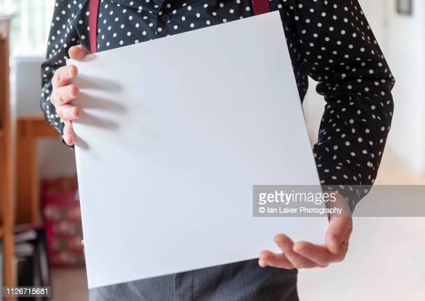 littlebourne, canterbury, england. 20 january 2019. plain white vinyl record or album cover being displayed and held by person in a domestic setting. - image stock-fotos und bilder