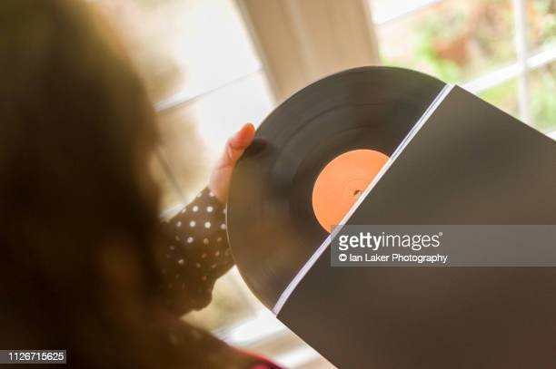 littlebourne, canterbury, england. 20 january 2019. removing vinyl record from inner sleeve, shot from above - printed sleeve stock pictures, royalty-free photos & images