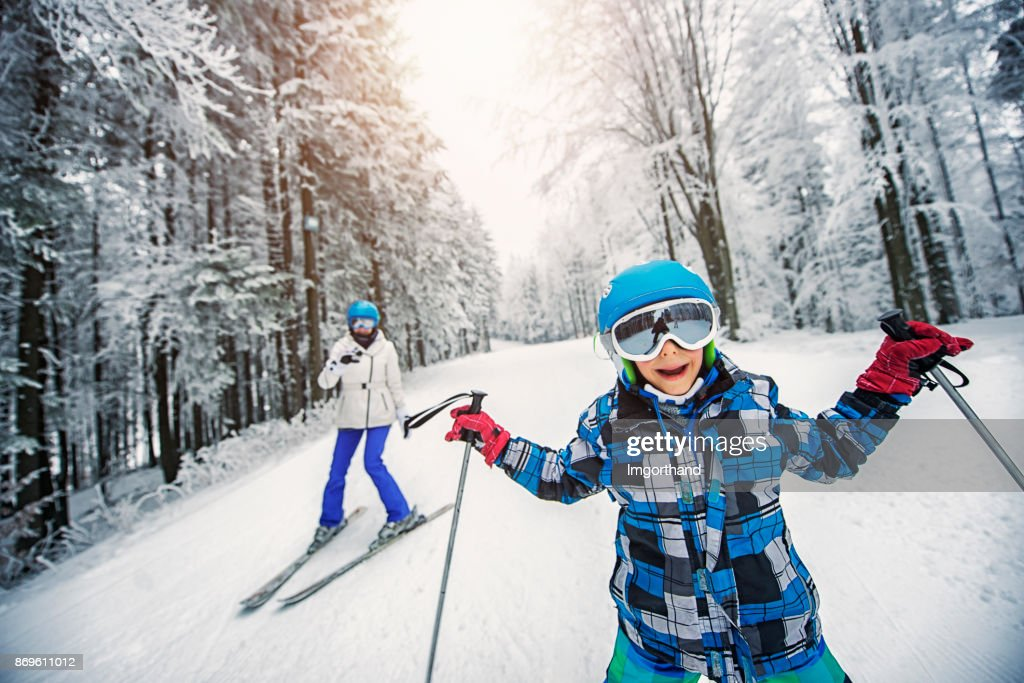 Littlo boy skiing with mother : Stock Photo