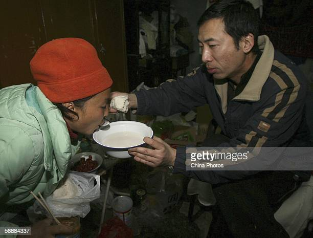 Liu Junluo husband of animal lover Duo Zirong feeds her soup when she only eats steamed bread as supper at home on February 14 2006 in Shanghai China...