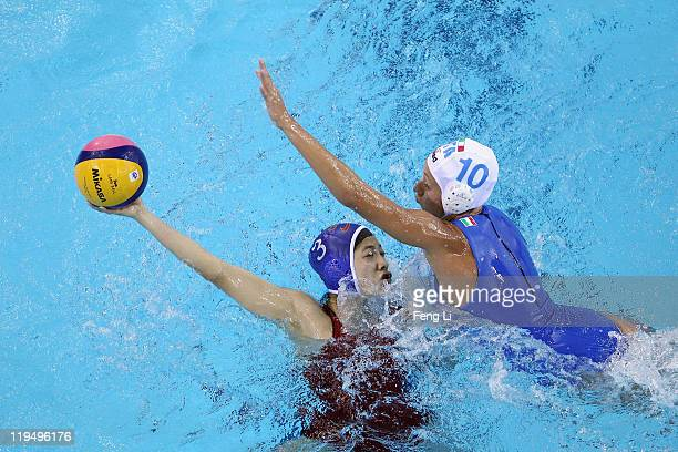 Liu Ping of China completes the ball with Giulia Rambaldi Guidasci of Italy in the Women's Water Polo first preliminary round match between China and...
