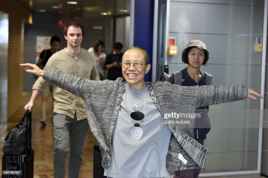 TOPSHOT - Liu Xia, the widow of Chinese Nobel dissident Liu Xiaobo, smiles as she arrives at the Helsinki International Airport in Vantaa, Finland, on July 10, 2018. - Despite facing no charges, the 57-year-old poet had endured heavy restrictions on her movements since 2010 when her husband won the Nobel Peace Prize -- an award that infuriated Beijing. (Photo by Jussi Nukari / Lehtikuva / AFP) / Finland OUT