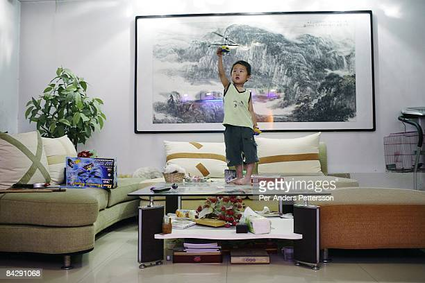 Liu Xing age 4 plays with his toy plane on a table in the living room of the family penthouse in a highrise building on June 3 2007 in central Xian...