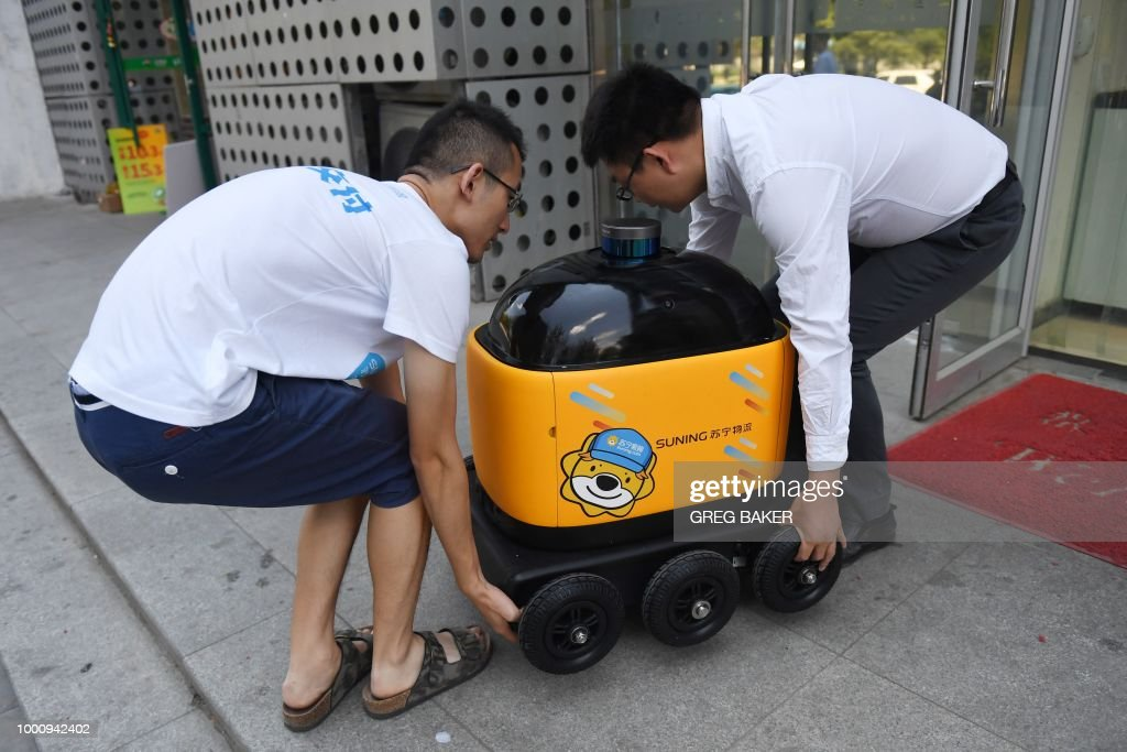 Liu Zhiyong (R) founder and CEO of Zhen Robotics, and a colleague carry a delivery robot out of a Suning supermarket during a demonstration of the robot in Beijing. - Along a quiet residential street on the outer edges of Beijing, a yellow and black cube about the size of a small washing machine trundles leisurely to its destination. This 'little yellow horse' is an autonomous delivery robot, ferrying daily essentials like drinks, fruit and snacks from the local store to the residents of the 'Kafka' compound in the Chinese capital. (Photo by GREG BAKER / AFP) / TO