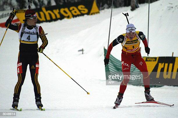 Liv Grete Poiree of Norway sprints to the finish line as Uschi Disl of Germany starts to celebrate in women's 125 km Mass Start in the World Cup...