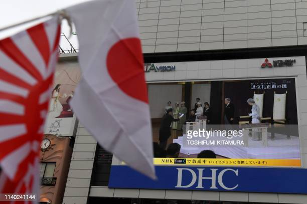 TOPSHOT A live broadcast of Japan's Emperor Akihito's abdication ceremony is shown on a big screen in Tokyo on April 30 2019 Emperor Akihito is...