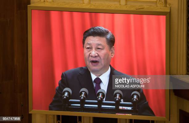 A live image of China's President Xi Jinping is seen on a screen as he delivers a speech during the closing session of the National People's Congress...
