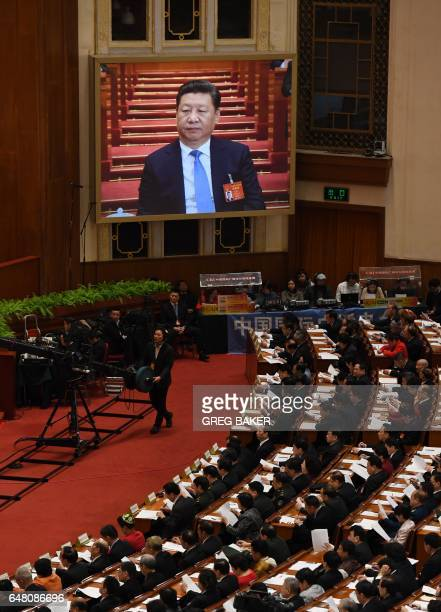 Live image of Chinese President Xi Jinping is seen on a screen above delegates as they listen to Premier Li Keqiang's speech during the opening...