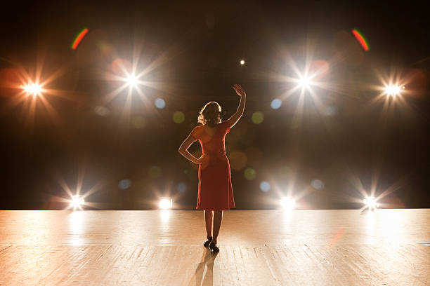 live performer standing on stage with lights - acting stock pictures, royalty-free photos & images