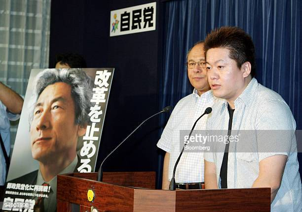 Livedoor President Takafumi Horie right speaks to reporters next to a poster of Japanese Prime Minister Junichiro Koizumi while Liberal Democratic...