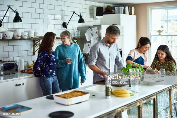 lively relaxed three generation family gathering in kitchen - family and happiness and diverse stock photos and pictures