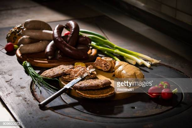 Liver sausage, blood sausage, spring onion, red radish, chives, mustard, bread on chopping board, hotplate