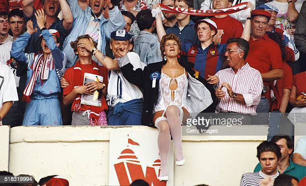 Liverpool and Everton fans share a joke with a scantily clad fan before the 1989 FA Cup Final between Everton and Liverpool at Wembley Stadium on May...