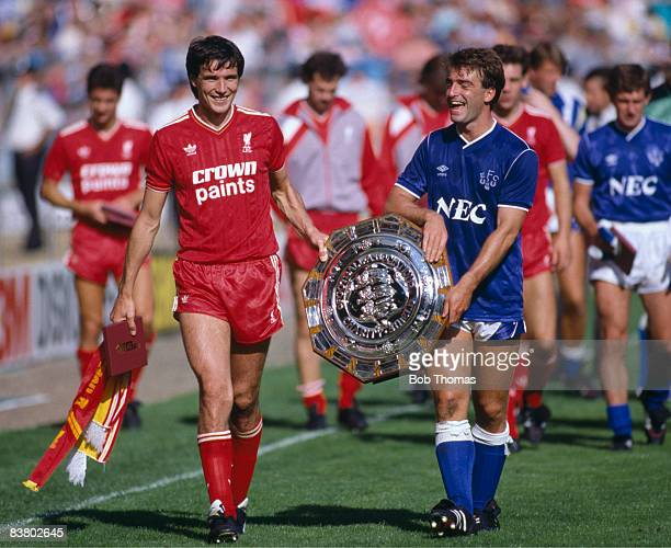 Liverpool captain Alan Hansen and Everton captain Kevin Ratcliffe carry the FA Charity Shield after the teams had drawn 11 at Wembley Stadium and the...