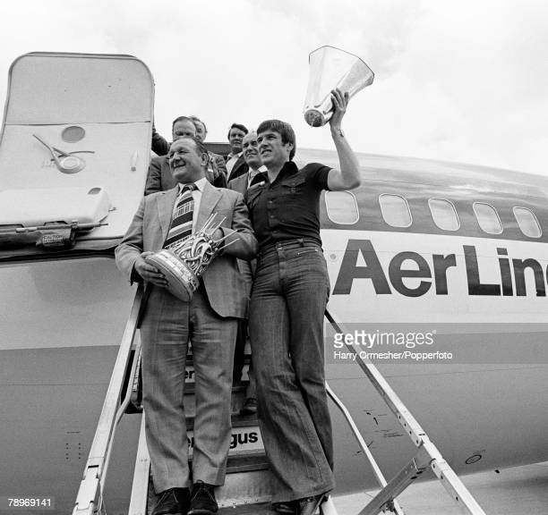 Liverpool captain Emlyn Hughes celebrates with the broken UEFA Cup trophy alongside manager Bob Paisley, as they disembark from an aeroplane at...