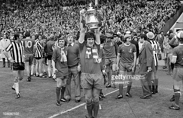 Liverpool captain Emlyn Hughes holds the F A Cup aloft at Wembey with Brian Hall, Ray Clemence, Steve Heighway and Phil Thompson in the background...