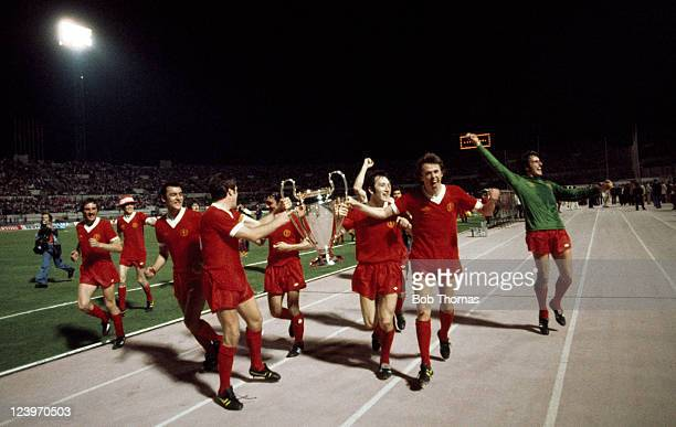 Liverpool captain Emlyn Hughes holds the trophy with Jimmy Case and Phil Neal during the lap of honour after their victory over Borussia...
