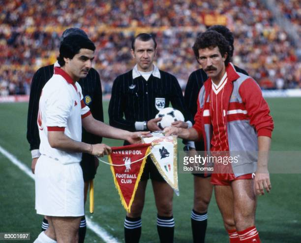 Liverpool captain Graeme Souness and Roma's Agostino Di Bartolomei exchange pennants watched by referee Erik Fredriksson before the European Cup...