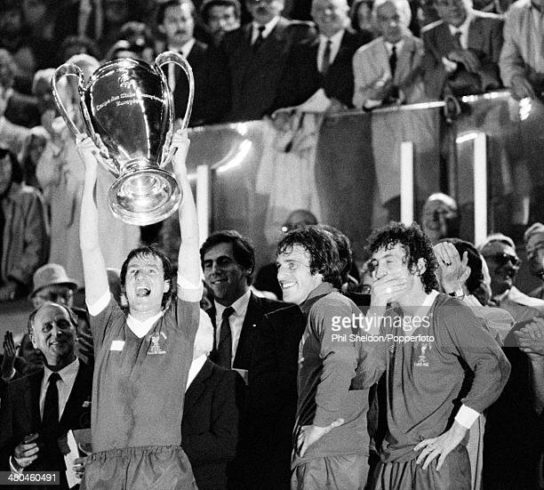 Liverpool captain Phil Thompson lifts the trophy watched by Ray Clemence and Terry McDermott after their 10 victory over Real Madrid in the European...
