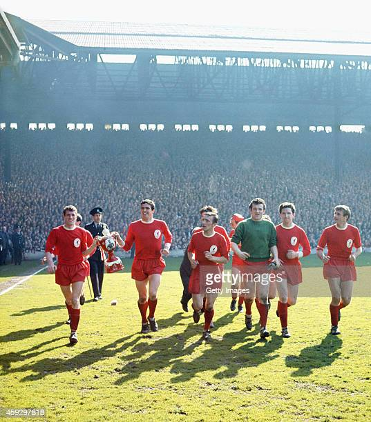 Liverpool captain Ron Yeats carrying a papermache model of the Championship trophy with his team mates after Liverpool seal the 1963/64 League...