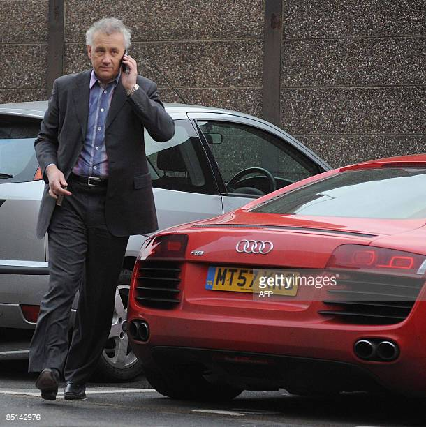 Liverpool chief executive Rick Parry uses his cellphone as he walks out Liverpool's Anfield ground on February 27 2009 Parry will leave his post as...