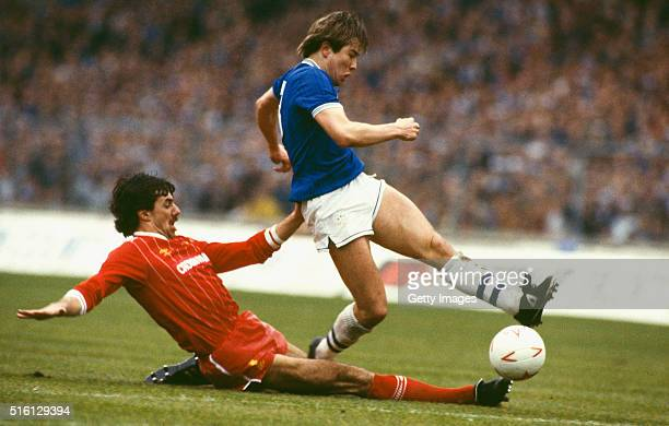 Liverpool defender Mark Lawrenson slides in on Everton striker Adrian Heath during the 1984 Milk Cup Final at Wembley Stadium on March 25 1984 in...