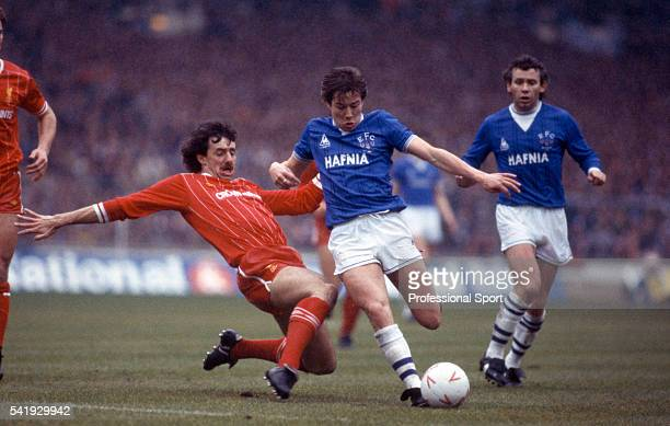 Liverpool defender Mark Lawrenson slides in to tackle Everton striker Adrian Heath watched by Peter Reid during the Football League Cup Final...