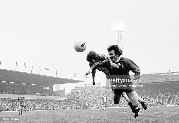 Liverpool defender Tommy Smith diving to head the ball in front of Birmingham City striker Peter Withe during their First Division match at St...