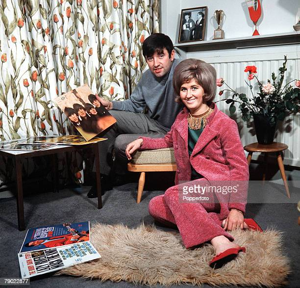 1965 Liverpool England Comedian and entertainer Jimmy Tarbuck is pictured at home with his wife Pauline holding the Beatles For Sale album in his...
