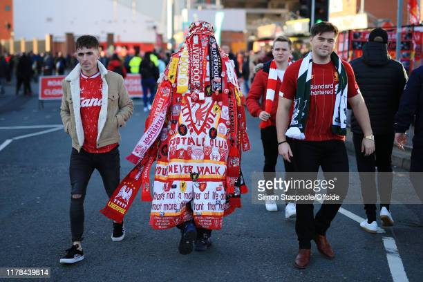 Liverpool fan adorned with scarves walks to the Premier League match between Liverpool FC and Tottenham Hotspur at Anfield on October 27 2019 in...
