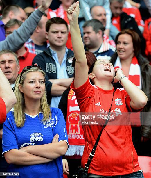 Liverpool fan as an Everton fan looks dejected after the FA Cup with Budweiser Semi Final match between Liverpool and Everton at Wembley Stadium on...