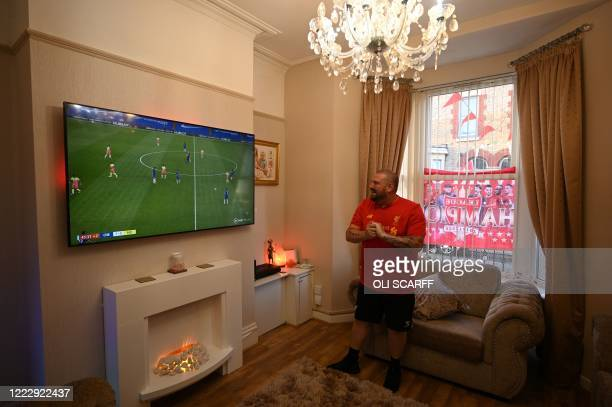 Liverpool fan Carl Williams watches the football in his fron room at his home in Liverpool north west England on June 25 as he waits for the result...