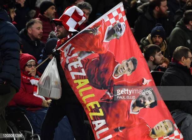 Liverpool fan carries a flag as he leaves following the English Premier League football match between Liverpool and West Ham United at Anfield in...