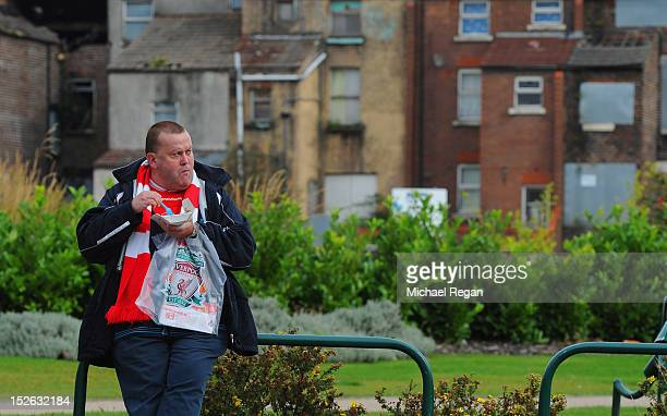 Liverpool fan eats fish and chips outside the ground before the Barclays Premier League match between Liverpool and Manchester United at Anfield on...