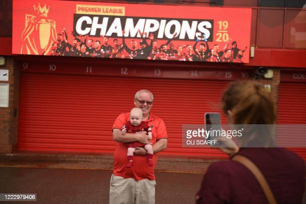 Liverpool fan Edward Milward holding his 9 week old grandson Harry, poses for a photograph beneath a new digital display celebrating Liverpool...