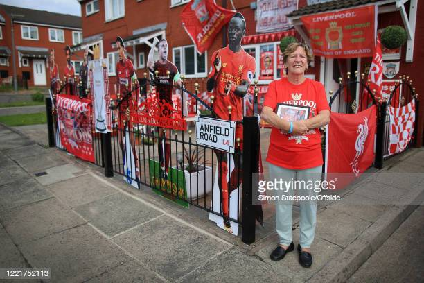 Liverpool fan Emily Farley poses outside her home which is decorated in club flags, banners and paraphernalia before the Premier League match between...