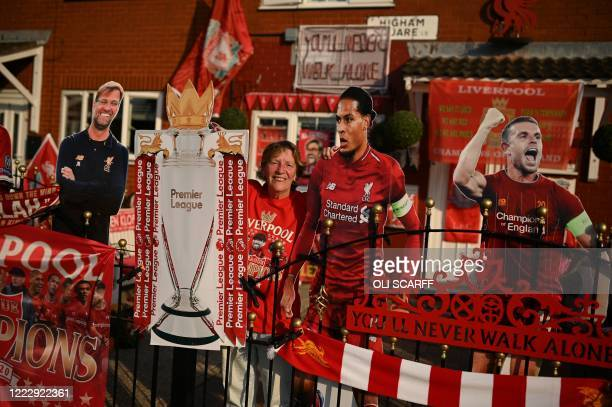 TOPSHOT Liverpool fan Emily Farley sits outside her home decorated with Liverpool banners and cut outs in Liverpool north west England on June 25 as...