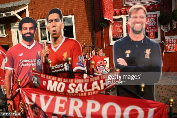 Liverpool fan Emily Farley sits outside her home decorated with Liverpool banners and cut outs in Liverpool north west England on June 25 as she...