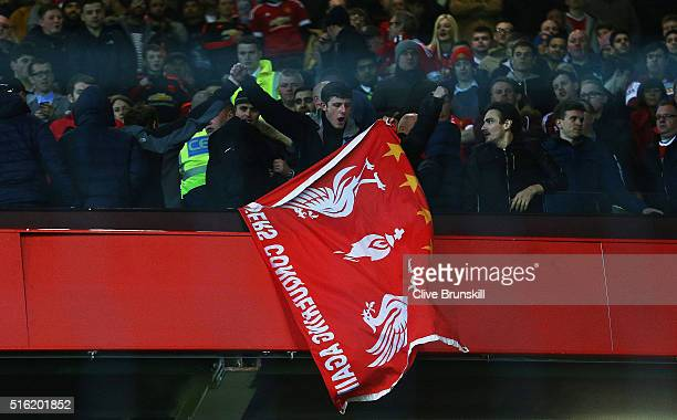 Liverpool fan holds a flag as he stands amongst Manchester United supporters after the UEFA Europa League round of 16 second leg match between...
