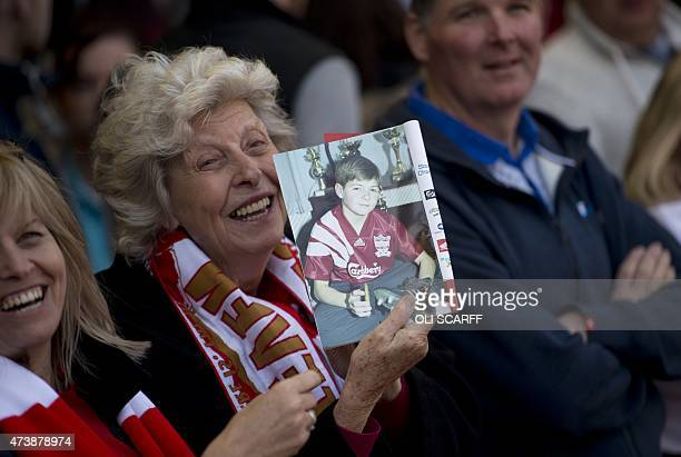 A Liverpool fan holds up an image of Liverpool's English midfielder Steven Gerrard as a child before the start of the English Premier League football...